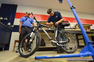 Ole Miss Bike Shop mechanic Stephen Valliant tightens the rear bag mount on one of several new bicycles to be used by Ole Miss Parking and Transportation staff as Traffic Officer Emanuel McJunkins looks on. Photo by Robert Jordan/Ole Miss Communications